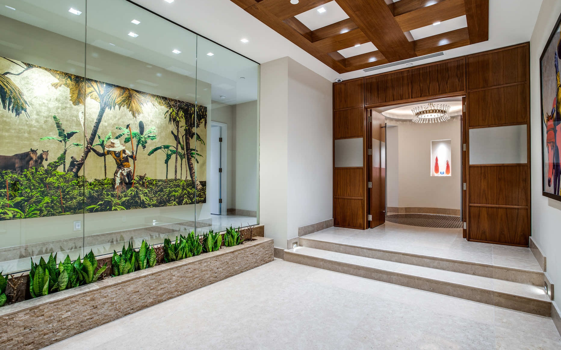 Dallas highrise foyer with planter and coffered ceiling detail; limestone floors throughout and a custom inlay in the floor under the chandelier in the round entry