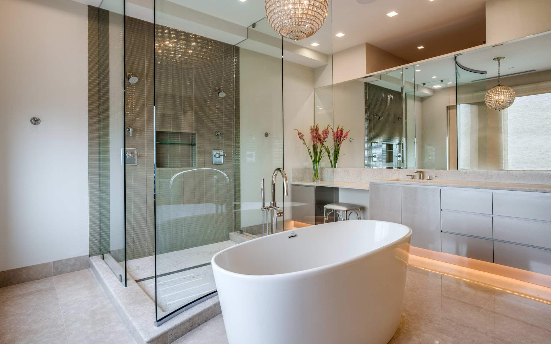 The master bath in this highrise condo new build has a huge walk-in shower for two and a stand-alone tub with a beautiful crystal chandelier to set off the space