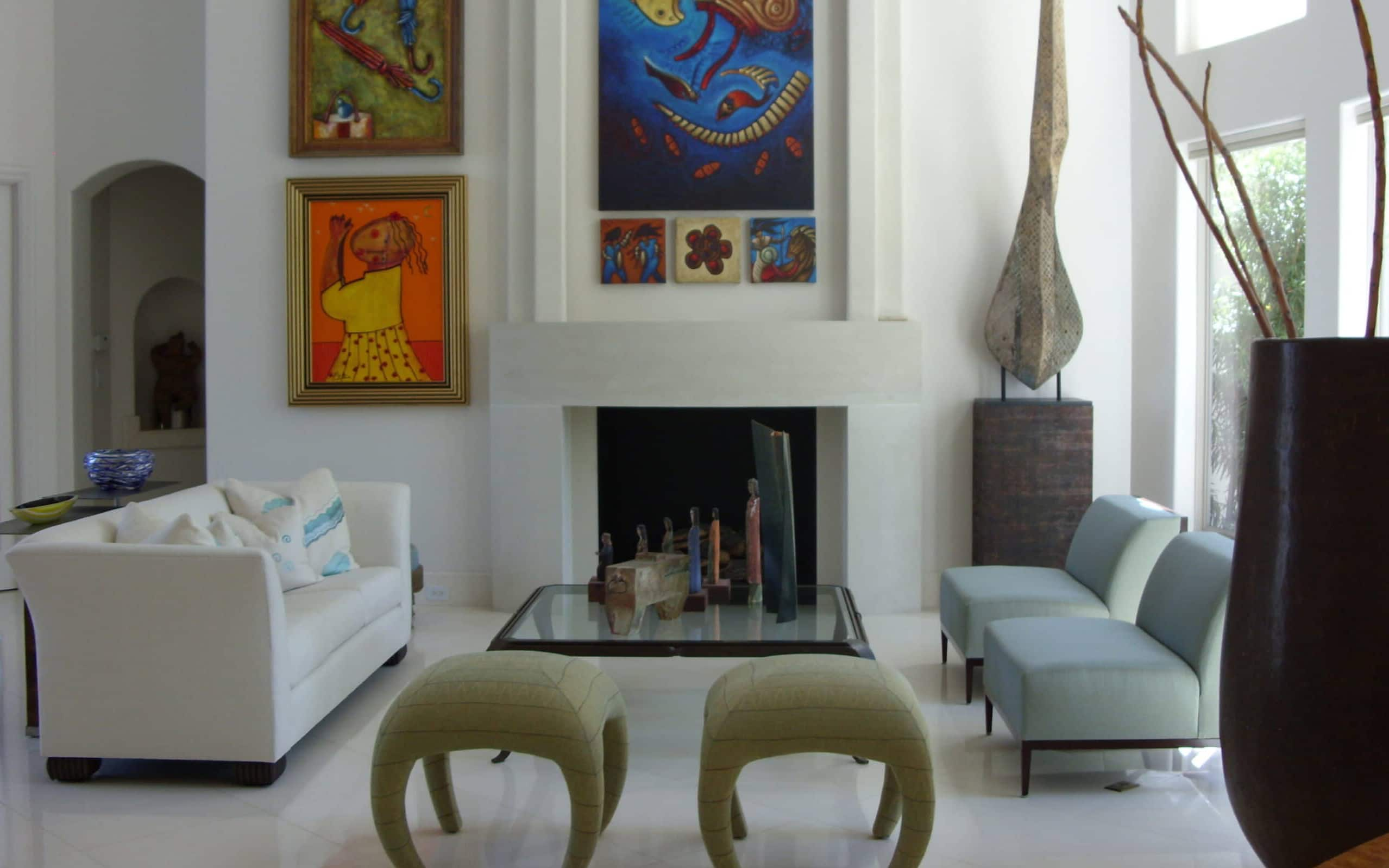 Off white walls make the art pop against a serene backdrop of pastels on the upholstery